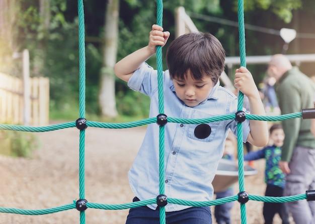 遊び場でロープを登るアクティブな子供、夏の晴れた日にクライミングアドベンチャーパークでアクティビティを楽しむ子供、屋外の遊び場で楽しんでいるかわいい男の子。