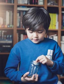 明確な瓶にお金のコインを保持している若い子供、彼の保存されたコインを数える子供、コインを持っている子供の手、将来の概念のための保存について学ぶ子供の低キー光肖像