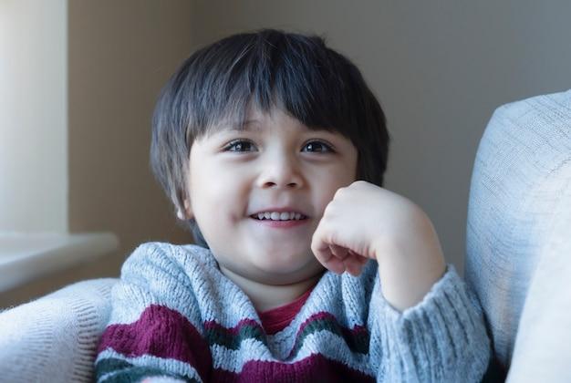 ソファーに座っていた肯定的な子供の肖像画