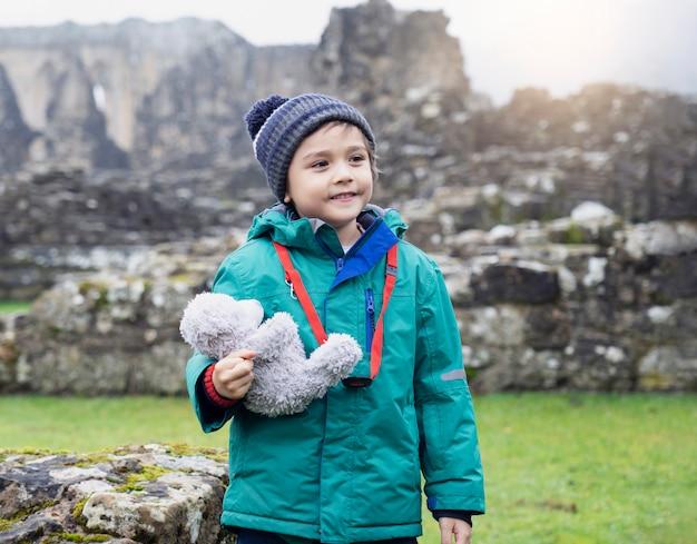 Портрет школьника принимая плюшевого мишку исследовать с его историей обучения, счастливый ребенок мальчик, одетый в теплую одежду, держа свою мягкую игрушку, стоял один с размытыми руинами