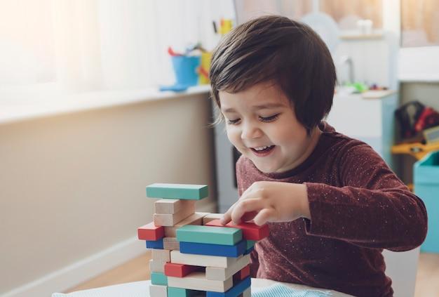 陽気な男の子の率直なショットは、プレイルームでカラフルな木製ブロックを再生し、自宅で木製のブロックを積み重ねる子供の肖像画、就学前と幼稚園の子供のための教育玩具。クリエイティブコンセプト