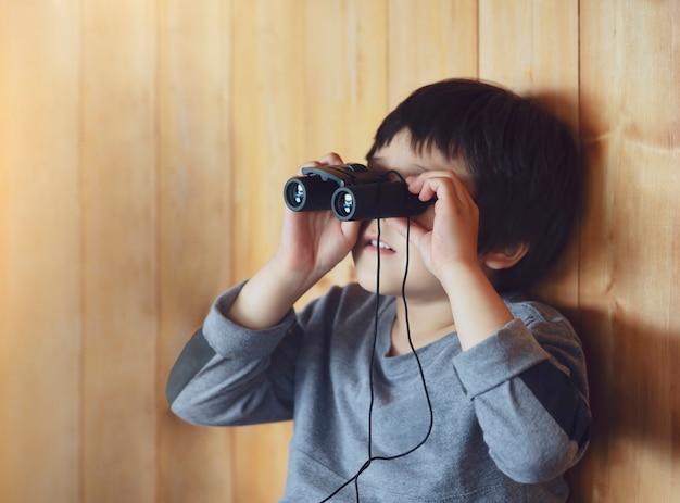 Портрет ребенка мальчик, глядя через бинокль в точке зрения животных станции, молодой исследователь с дикой природой в летнем лагере