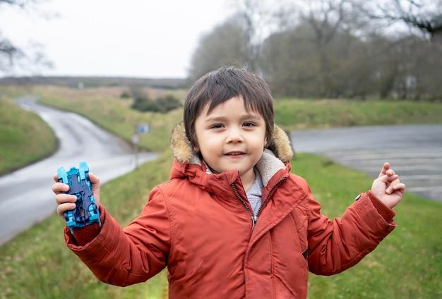 Портрет школьника исследовать и изучать природу с школьной поездкой в мрачной осени, счастливый ребенок мальчик, держа его игрушку автомобиля, носить теплую одежду, стоял один с размытыми полями фермы.