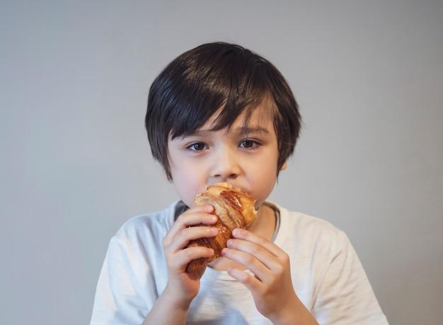 朝学校に行く前に彼の朝食のための子少年クロワッサン