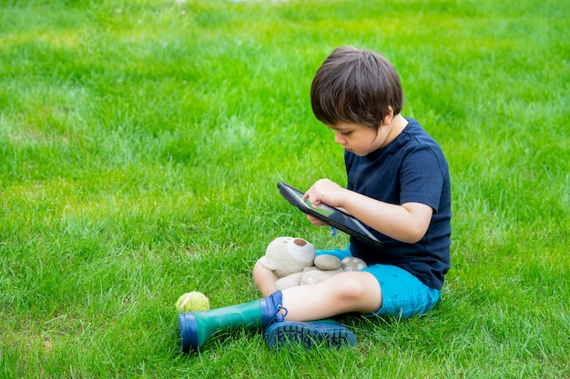 Малыш сидит на траве и играет в игры на планшете