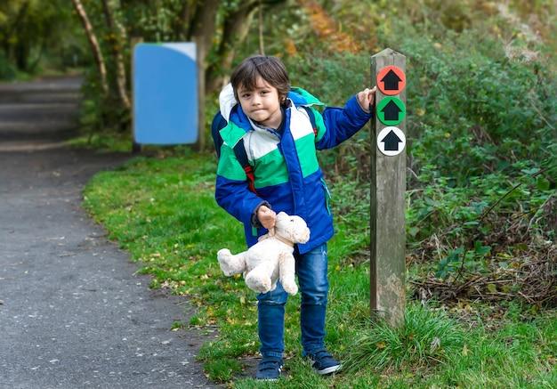 方向矢印記号に人差し指を探しているテディベアを保持している屋外のポートレートの子供