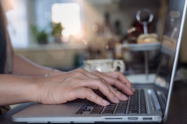 Женщина дела азиатская используя портативный компьютер работая в кухне
