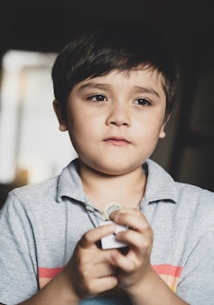 思考の顔でお金を保持している一人で立っている肖像画少年