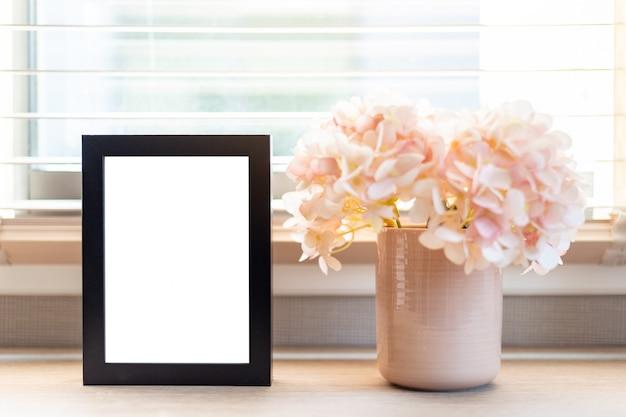 ノートパソコンと花とデスクトップのテーブル作業スペースに空白の黒い枠