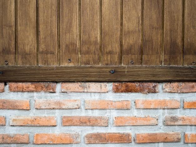 板の木製の壁は古いレンガの壁にあります
