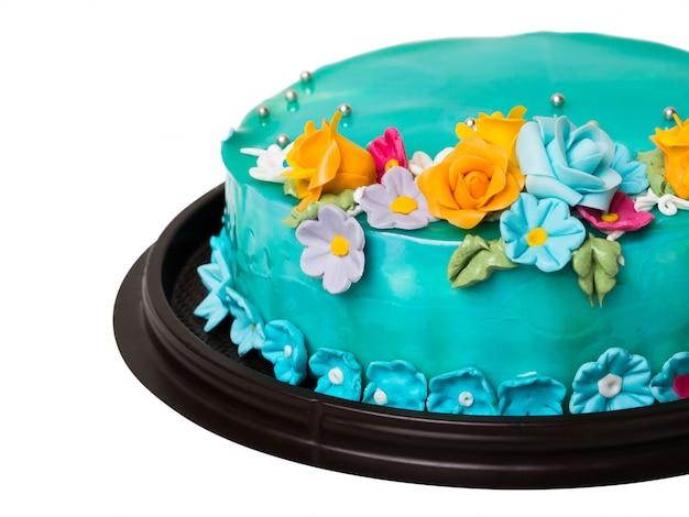 白い背景の上のカラフルなアイシングフルーツとクローズアップブルーオーシャンジャムケーキの装飾