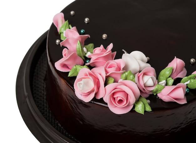 白地にカラフルなアイシングフルーツとクローズアップダークチョコレートケーキの装飾