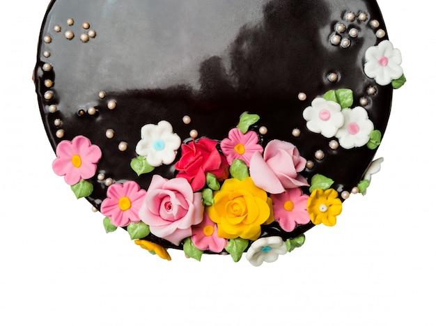 トップビュークローズアップ白地にカラフルなアイシングフルーツとチョコレートケーキの装飾