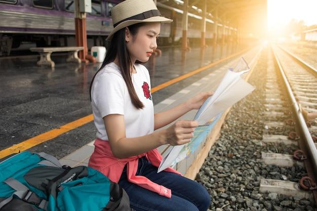女性、座って、夏の列車駅で地図を表示