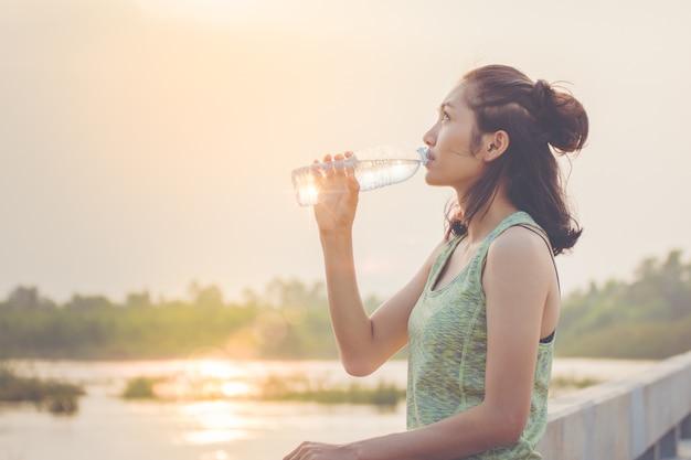 運動後にアジアの女の子がミネラルウォーターを飲んでいる
