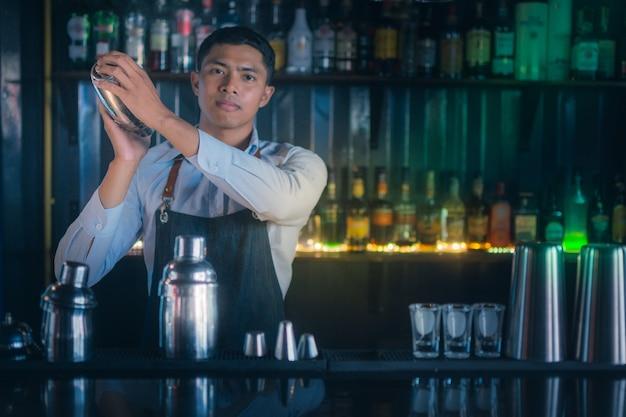 Молодые азиатские литейные бармены встряхивают ингредиенты коктейля,