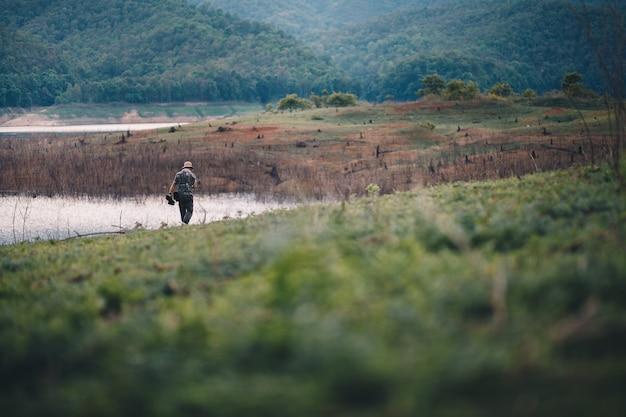 Человек, посещающий зеленый лес