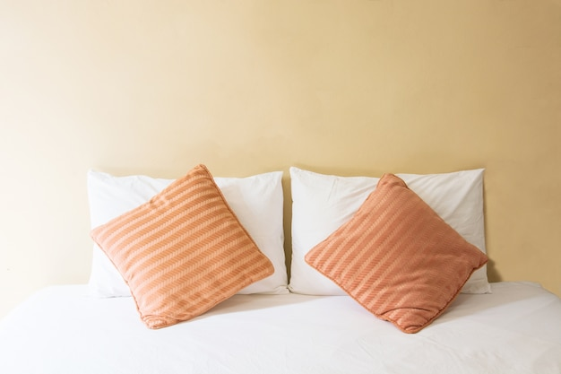 Белая подушка и оранжевая подушка на кровати и с одеялом в винтажной спальне