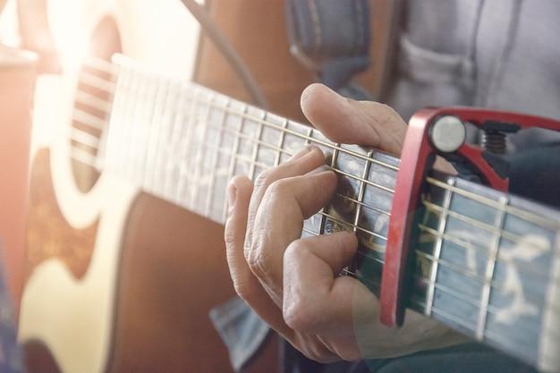 Крупный план человеческих рук, играющих на акустической гитаре, мягкий винтажный стиль