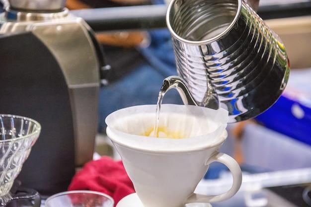 バリスタこぼれるお湯は銀のティーポットからフィルターをかけられたコーヒーを準備します