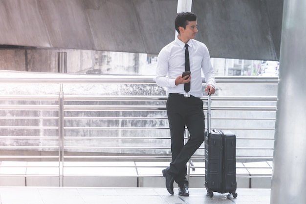 Деловой турист с багажом использует свой мобильный телефон