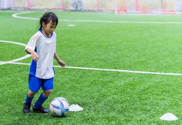 小さなアジアの女の子が屋内のサッカーフィールドでトレーニングしています