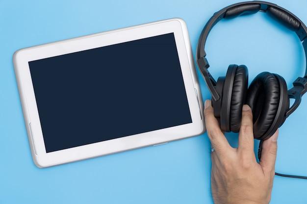 音楽とビデオストリーミングのコンセプトのためのヘッドフォンを持っている手で空のタブレット