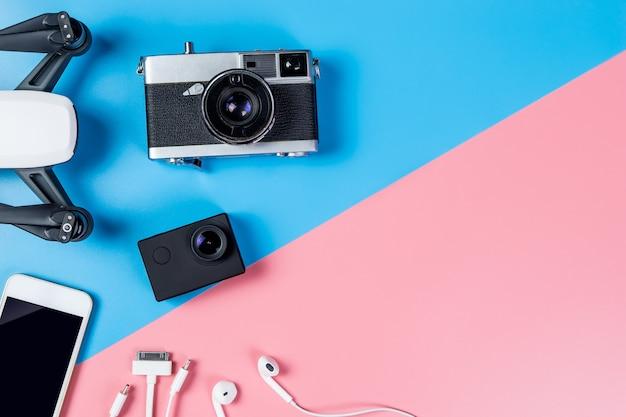Привет технологий гаджета путешествия и аксессуары на синем и розовом пространстве копирования