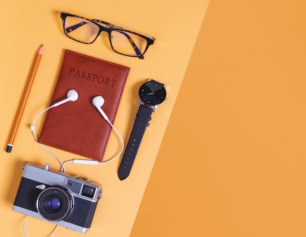 旅行オブジェクトとパスポートカメラと飛行機とオレンジ色の背景上のアクセサリー