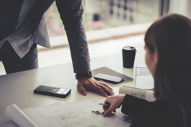 女性建築家は彼女の上司に不動産建築計画を見せています。