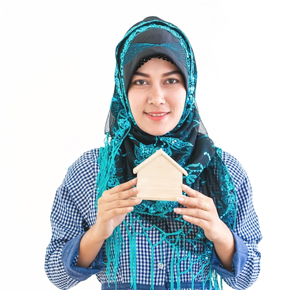 イスラム教徒の女性は住宅コンセプトの家モデルを保持しています。
