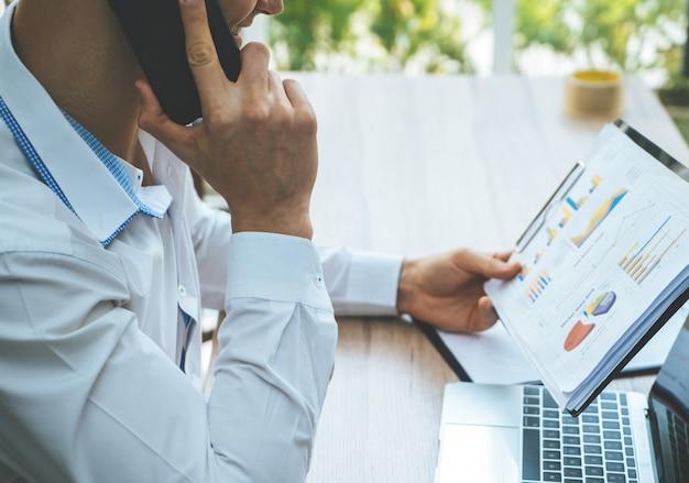 ビジネスの男性は電話通信に関するレポートをチェックしています