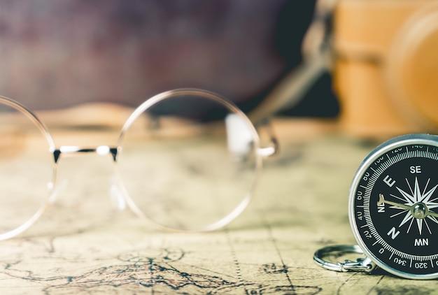 ビンテージ眼鏡とエクスプローラー旅行の概念のためのコンパス