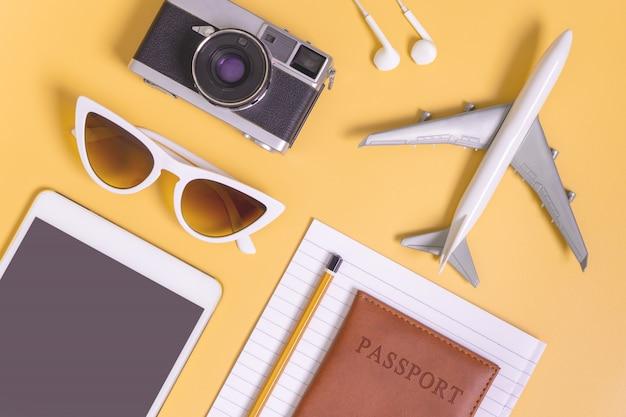 Плоский объект путешествия лежал на желтом фоне для концепции путешествия