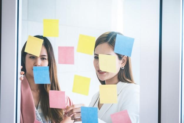 カジュアルな創造的なビジネスの女性は窓に理想と目標を書いています。