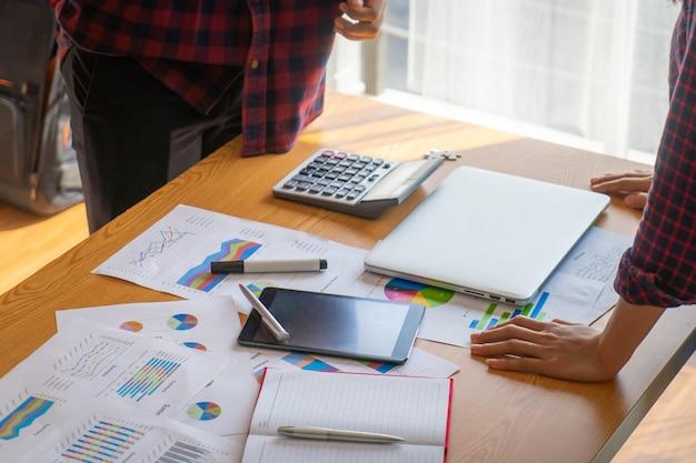 机の上の事業報告書について議論するチーム