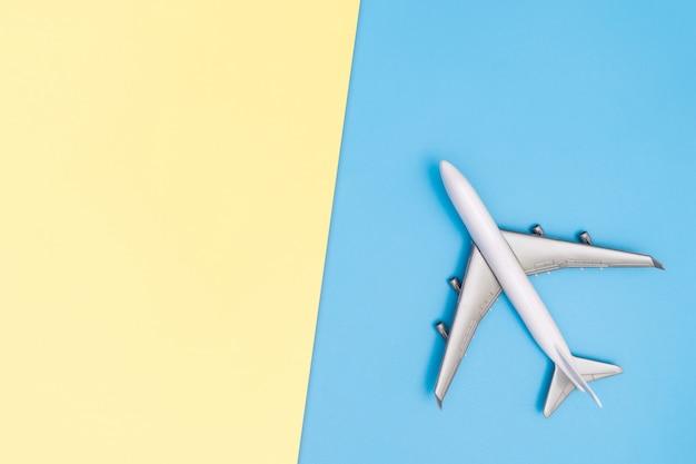 おもちゃの飛行機は青ピンク黄色の世界概念を旅行します。