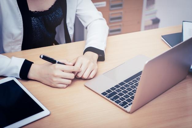 ビジネスの女性のビジネスホームオフィスでラップトップを使用して