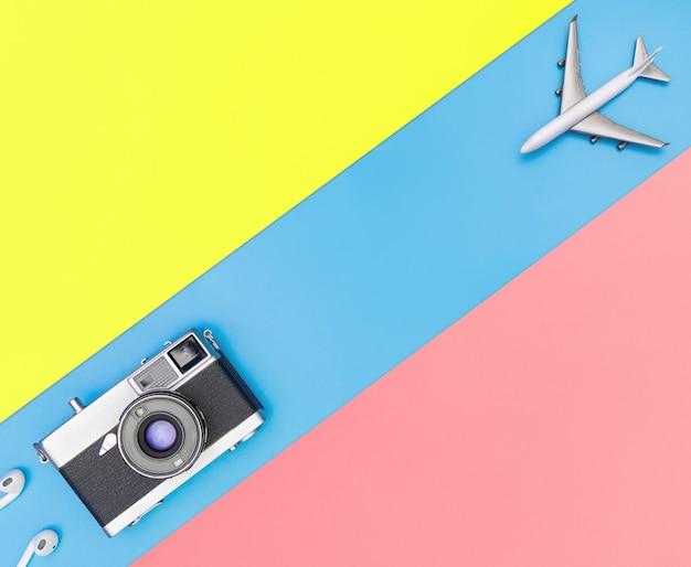 Белый игрушечный самолет и камера на синем и желтом розовом фоне