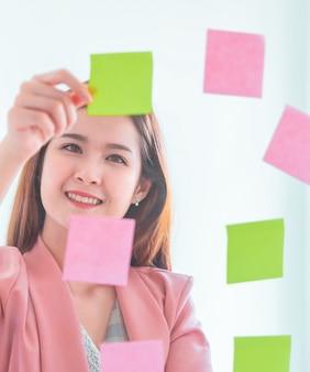 カジュアルな創造的なビジネス女性が窓に理想と目標を書いています。