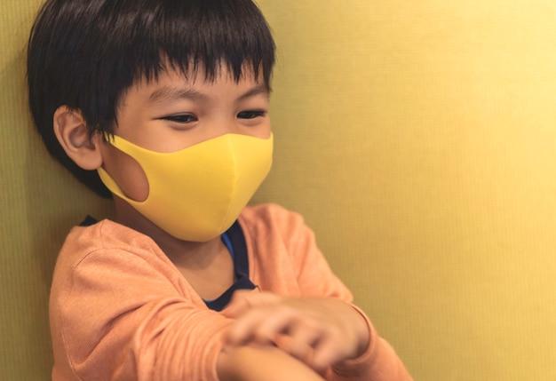 小さな男の子はインフルエンザから健康的なマスク保護を身に着けています。