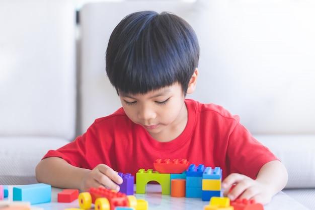 おもちゃのブロックを手でリビングルームで遊ぶ少年