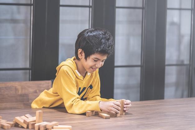 小さな男の子は木のおもちゃブロックタワーを構築します。
