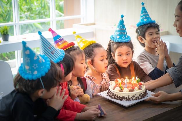 子供たちのグループは、誕生日パーティーの誕生日ケーキを吹いています。
