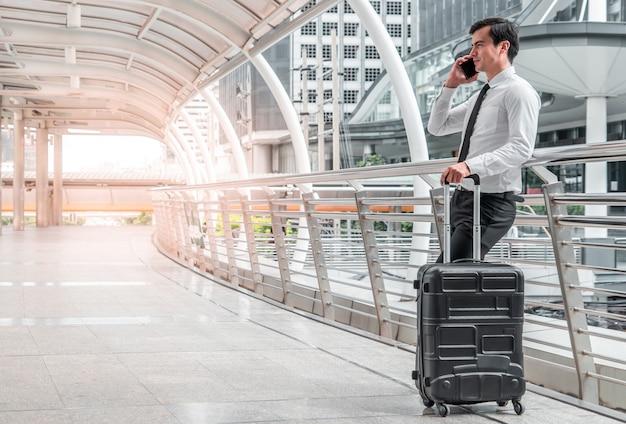 Молодой человек деловой человек в командировке, стоя с его багажом и сделать звонок за пределами аэропорта.