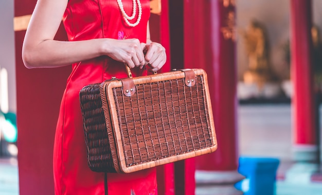 木製の荷物を持つアジアの中国の女の子ビンテージアジア旅行の概念