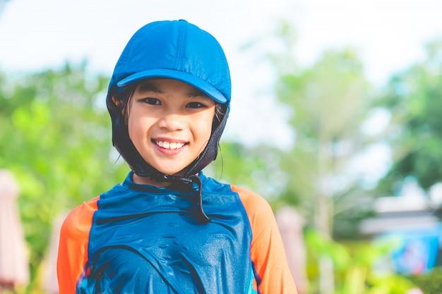 小さな女の子の肖像画は、スイミングプールで遊んでいます。