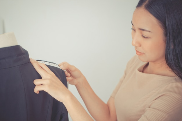 ファッションデザイナーの手は測定テープで肩を測定しています