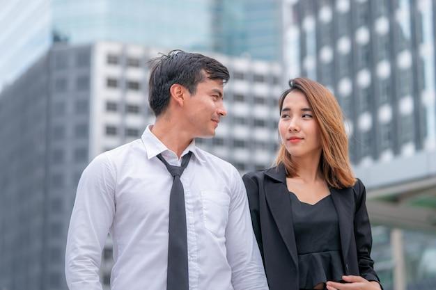 オフィスの恋人のカップルは近代的な都市鉄道駅で一緒に歩いています。
