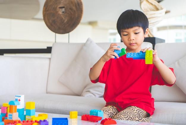 アジアの少年がリビングルームのテーブルの上のおもちゃのブロックをスタッキング